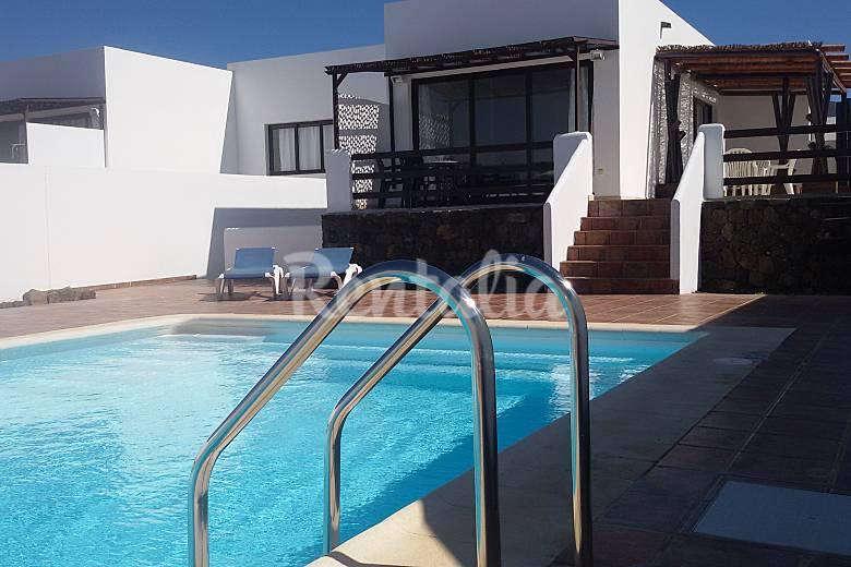 Casa con gran piscina y doble terraza playa blanca for Apartamentos con piscina y playa